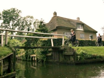 Women in traditional Dutch dress are cycling in Giethoorn