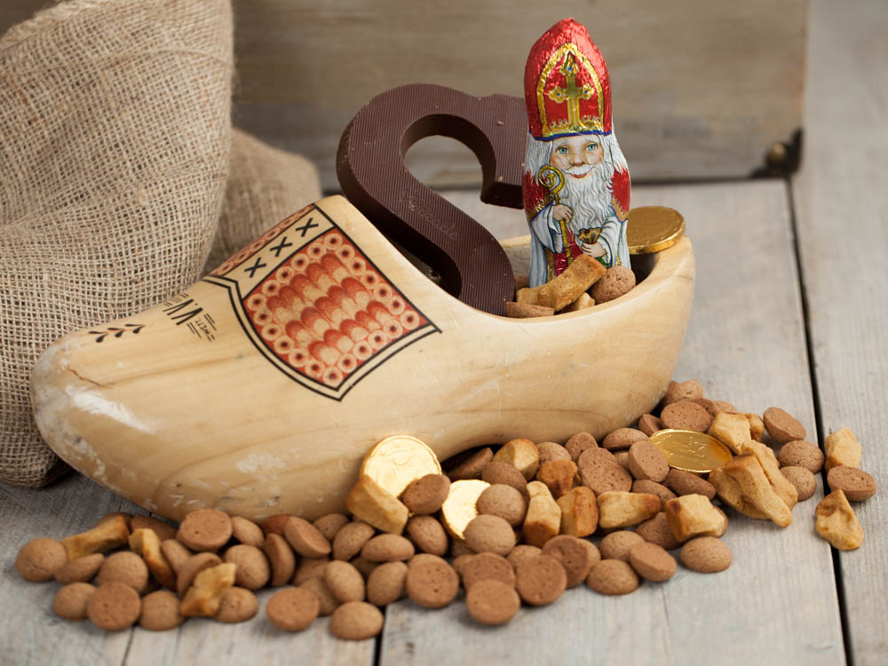 A wooden shoe filled with Saint Nicholas delicacies such as Choclate Letters, Pepernuts, Spicy nuts, and choclate coins.