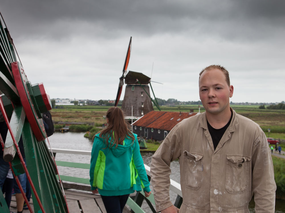 A young miller standing on a Dutch Windmill
